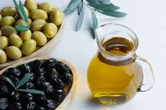 Glass bottle of olive oil and olive tree branch, raw turkish green olive seeds. And leaves on white table. green olives background, olivae oleum stock photo