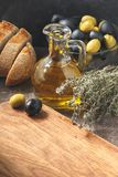 Glass bottle of olive oil with olives. Glass bottle of premium virgin olive oil, bowl with olives, bread and herbs over dark background, rustic style Royalty Free Stock Photos