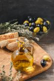 Glass bottle of olive oil with olives. Glass bottle of premium virgin olive oil, bowl with olives, bread and herbs over dark background, rustic style Stock Images