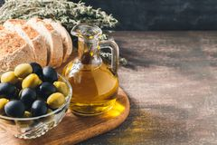Glass bottle of olive oil with olives. Glass bottle of premium virgin olive oil, bowl with olives, bread and herbs over dark background, rustic style Royalty Free Stock Photography