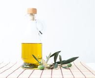 Glass bottle of olive oil. Glass bottle of olive oil and some olives with leaves isolated on a white background Royalty Free Stock Photo