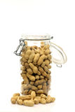 Glass bottle with peanuts. Glass bottle with lots of peanuts in and around it Royalty Free Stock Photos