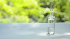 A glass bottle with a pipette filled with whey stands on a white table against a background of trees swaying from a wind stock footage