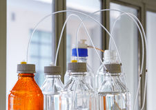 Glass bottle with plastic hose. Close up clear and amber color bottle with plastic hose for High performance liquid chromatography - HPLC Stock Photography
