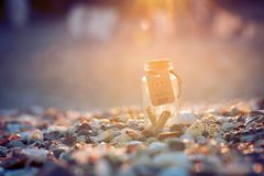 Glass bottle potion of happy on shells abstract. Nice bottle creative 100 perstent happy  vacation Royalty Free Stock Photography