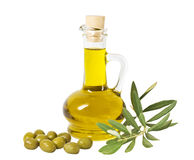 Glass bottle of premium olive oil and some olives with a branch isolated. On white background Stock Photos