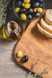 Glass bottle of olive oil with olives. Glass bottle of premium virgin olive oil, bowl with olives, bread and herbs over dark background, rustic style Stock Photos