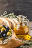 Glass bottle of olive oil with olives. Glass bottle of premium virgin olive oil, bowl with olives, bread and herbs over dark background, rustic style Royalty Free Stock Photo