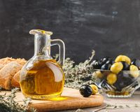 Glass bottle of olive oil with olives. Glass bottle of premium virgin olive oil, bowl with olives, bread and herbs over dark background, rustic style Royalty Free Stock Images