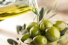 Glass bottle of premium virgin olive oil and some olives with le. Aves royalty free stock photos