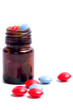 Glass bottle with red and blue pills Royalty Free Stock Images