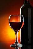 Glass and bottle of red wine. Over dark red background Stock Images