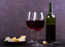 Glass and bottle of red wine, cheese, bread, garlic, nuts, salami on gray stone texture background. Stock Image