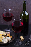 Glass and bottle of red wine, cheese, bread, garlic, nuts, salami on gray stone texture background. Royalty Free Stock Images
