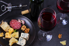 Glass and bottle of red wine, cheese, bread, garlic, nuts, salami on gray stone texture background. Royalty Free Stock Photos