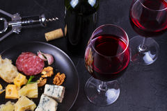 Glass and bottle of red wine, cheese, bread, garlic, nuts, salami on gray stone texture background. View from above. Stock Photos