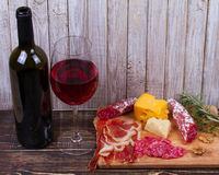 Glass and bottle of red wine, cheese, salami, walnuts, prosciutto and rosemary on wooden background Royalty Free Stock Photography