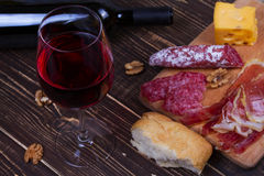 Glass and bottle of red wine, cheese, salami, walnuts, prosciutto and rosemary on wooden background Stock Photography