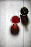 Glass and bottle of red wine with cork on table Stock Image