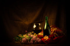 Glass and Bottle of Red Wine in Elegant Setting Stock Images