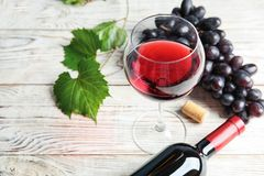 Glass and bottle of red wine with fresh ripe juicy grapes. On table stock images