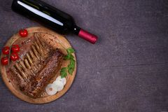 Glass and bottle of red wine with lamb chops. Wine and meat. Wine and food conception. View from above, top, horizontal royalty free stock image