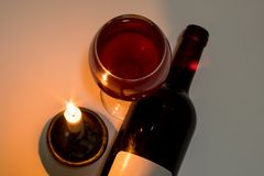 A glass and a bottle of red wine next to a burning candle stock images