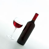 Glass and bottle of red wine unusually on white Stock Images