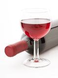 Glass and bottle of red wine unusually on white Stock Photo