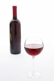 Glass and bottle of red wine unusually on white Royalty Free Stock Photos