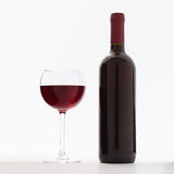 Glass and bottle of red wine unusually on white Stock Image