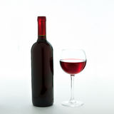 Glass and bottle of red wine unusually on white Royalty Free Stock Images