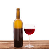 Glass and bottle of red wine unusually on wooden Stock Photography