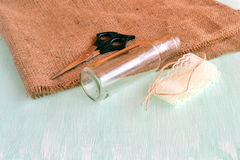 Glass bottle, scissors, burlap, lace. Set for handmade vase. How to make vase. Simple and cheap DIY recycled material Royalty Free Stock Image