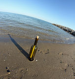 Glass bottle with a secret message on the shore of beach Royalty Free Stock Photos