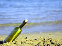 Glass bottle with a secret message on the shore of beach Royalty Free Stock Image