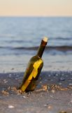 Glass bottle with a secret message. On the shore of sandy beach Stock Image