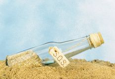 A glass bottle with SOS in sand. On a blue background Royalty Free Stock Photos