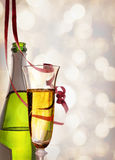 Glass and bottle of sparkling white wine and ribbons hanging Stock Image