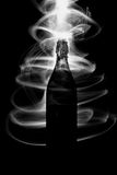 Glass bottle with sparks and waves of light Royalty Free Stock Images