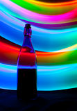 Glass bottle with sparks and waves of light Stock Photography