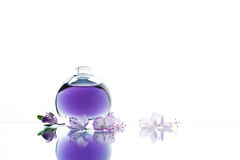 Glass bottle with violet liquid and flowers Stock Photo