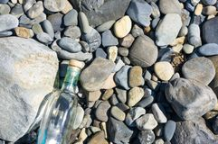 Glass bottle washed up by the sea. On a pebble beach Stock Photography