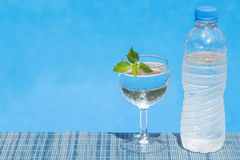Glass and bottle of water on bamboo straw mat Royalty Free Stock Image