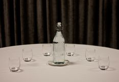 A glass bottle of water with a saucer and glasses placed on a table covered by white tablecloth. In the background a grey curtain. stock image