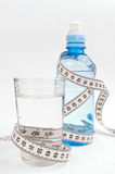 Glass and bottle of water, wrapped with centimeter Royalty Free Stock Images