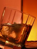 Glass and bottle of whiskey. Glass of whiskey over red background royalty free stock photos