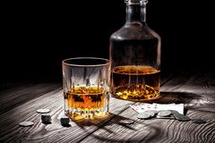 Glass and bottle of whiskey and playing cards and Stock Photos