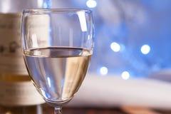 Glass and bottle white wine on blink light. Background stock photo