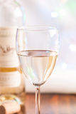 Glass and bottle white wine on blink light. Background royalty free stock photo